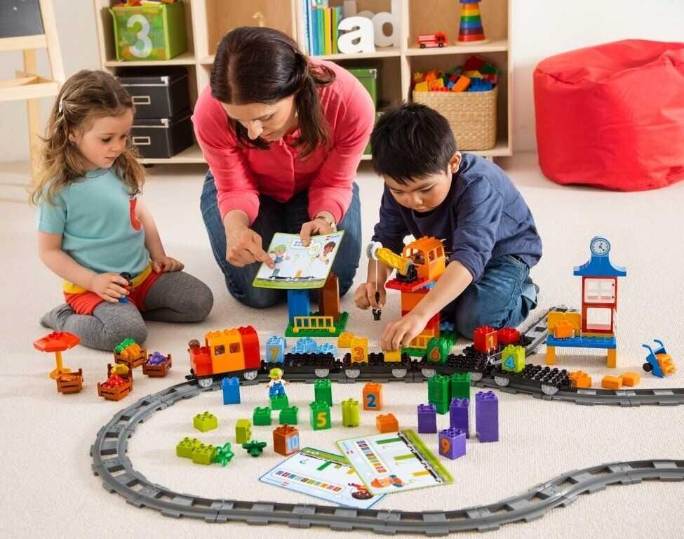 Дети играют с мамой с железной дорогой