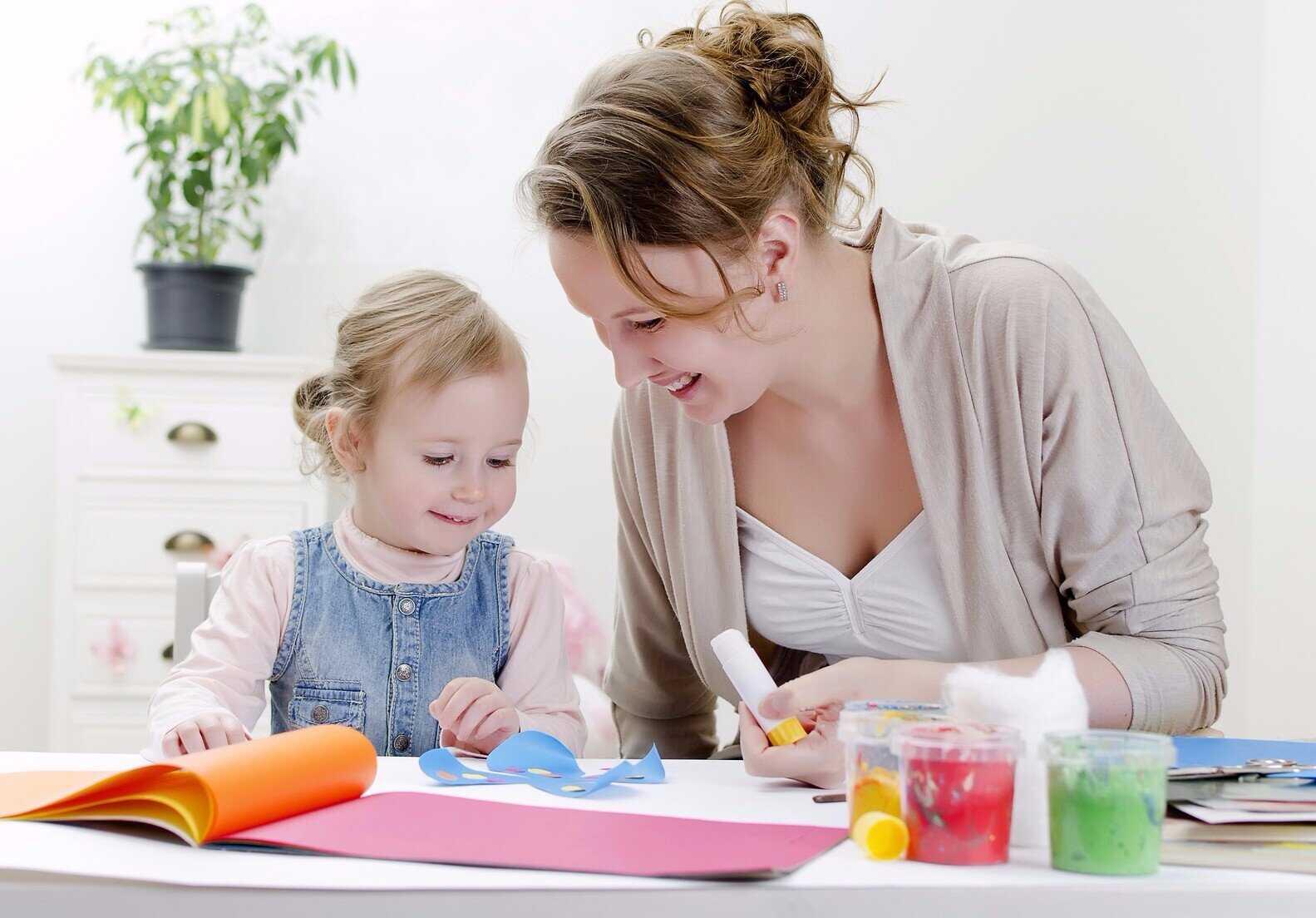 Девочка делает аппликацию с маминой помощью
