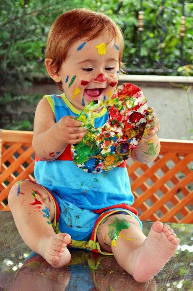 Малыш играет с красками