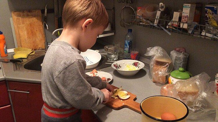 Ребёнок помогает нарезать яйца
