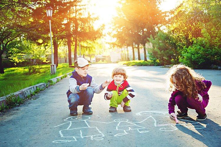 Дети рисуют мелками на асфальте сказку